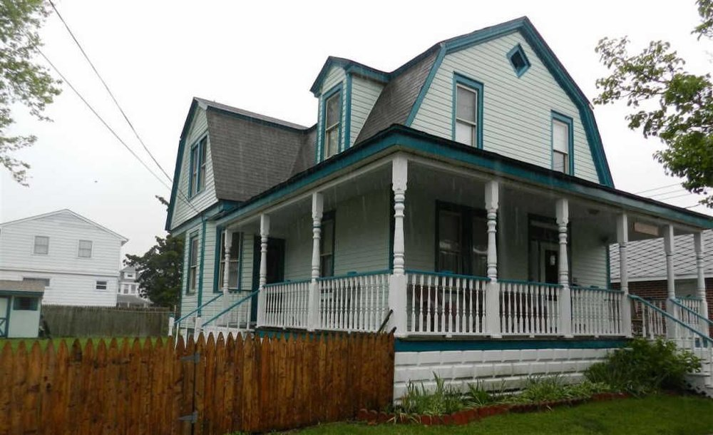Gambrel roof Victorian. Notice name plaque hanging above porch stairs. In the past, many owners named their homes.