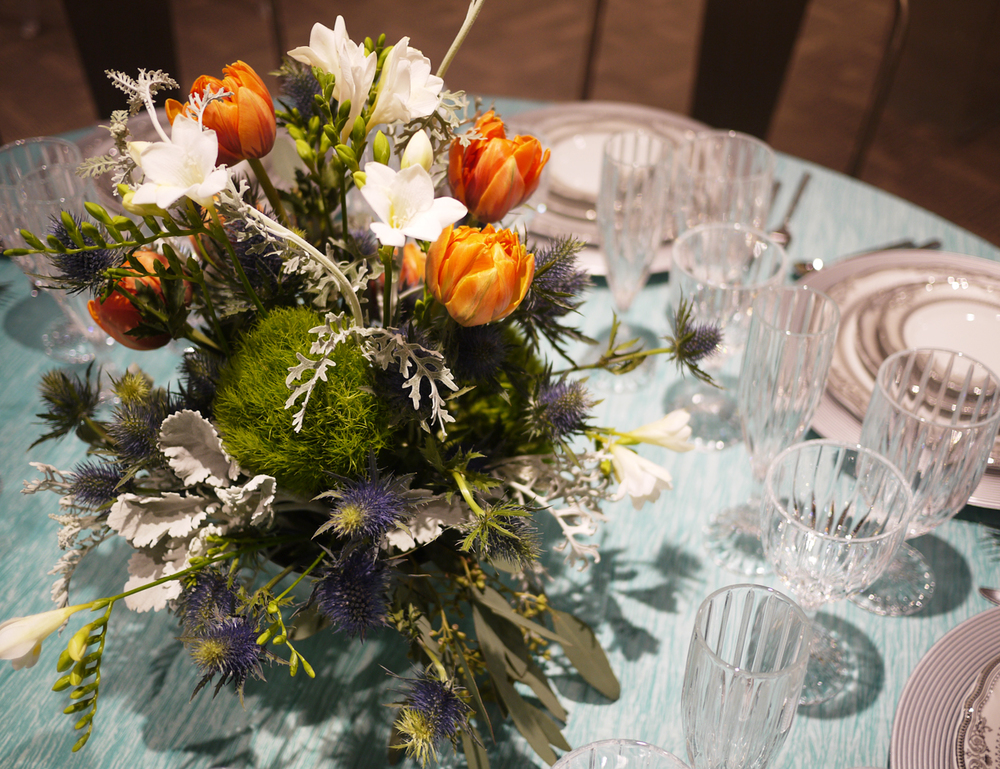 We used a beautiful vintage silver compote for this arrangement of tulips, freesia, dianthus, sea holly, eucalyptus, and dusty miller. A very unique combination to complement the table setting from Alpine Party Rentals.