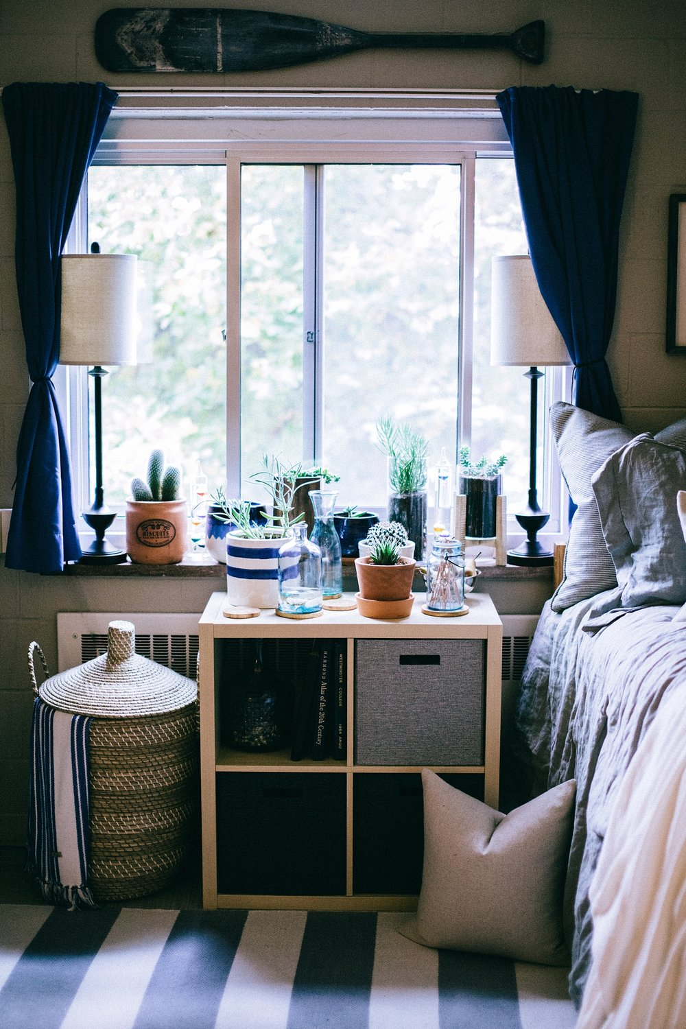 One of the biggest things for college students is finding a place to put  stuff .  Chris has found the balance between functionality and usability under his window with the  Kallax Shelf Unit from Ikea .  This piece simultaneously acts as a nightstand, storage, and plant stand.