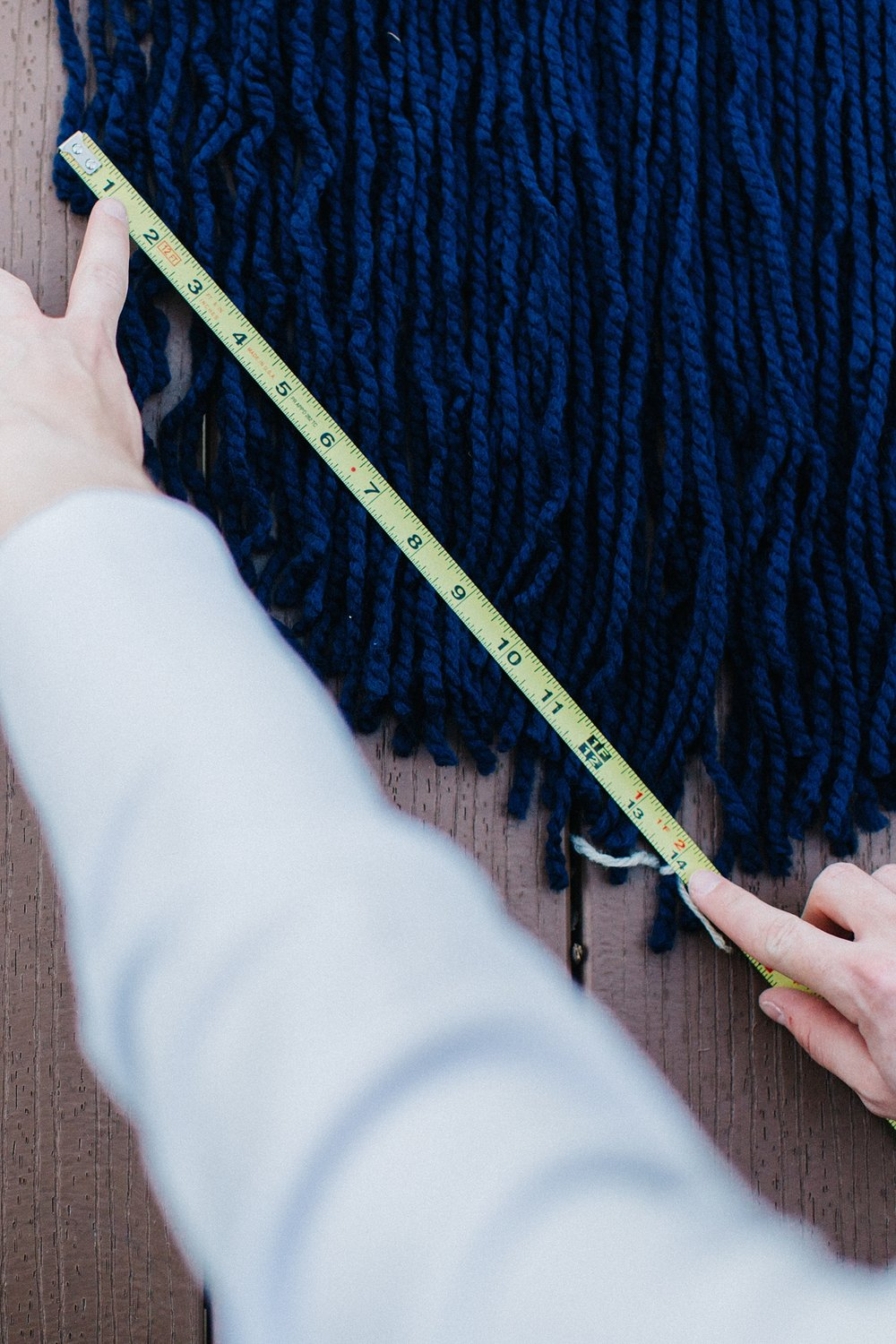 Step 7:    Mark out the center  string (here we tied some white yarn on the center to mark it.  Then using your tape measure to create a straight edge to cut a taper.