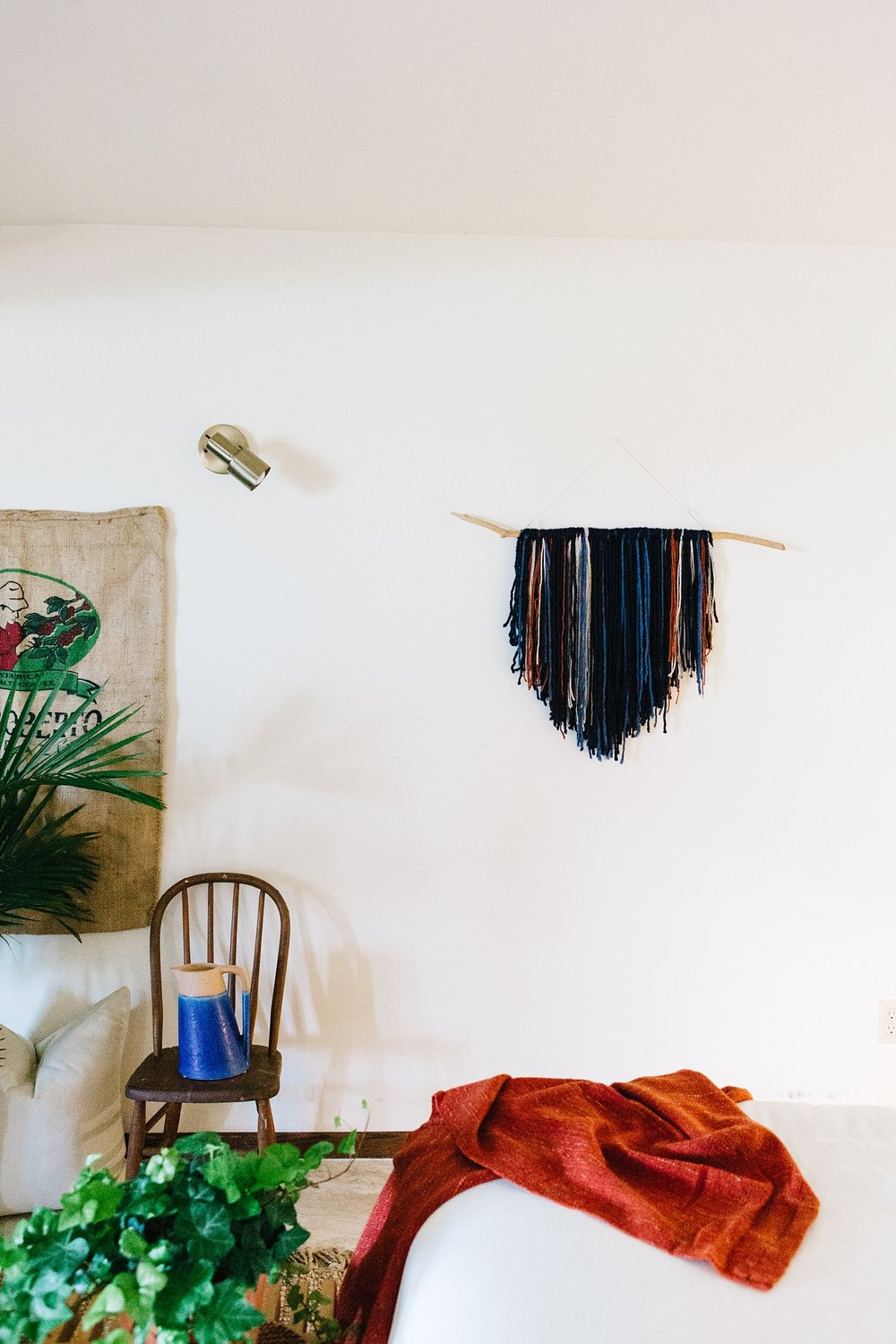 Notes of orange in the boho wall hanging are picked up from the burnt terracotta throw at the foot of the bed. I chose a dominant color of navy for the wall hanging, and sporadically inserted other colors of blue, orange, and beige to add depth and texture.