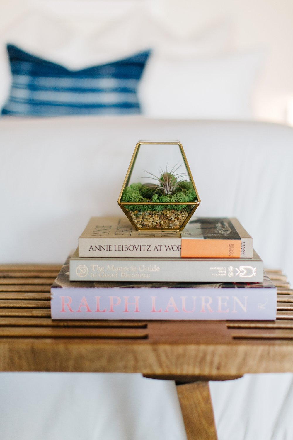 Symmetry continues to play a huge role in this space. Atop this teak bench found at an antique mall are some favorite books along with a miniature terrarium housing an air plant.