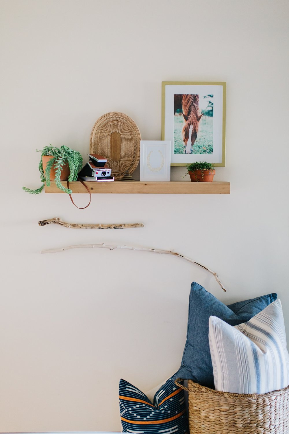 A variety of textures come together on this floating shelf: a woven artist signed basket, a succulent in a refined shaped terracotta clay pot, framed art, a beach stone, and a vintage restored aluminum Polaroid SX-70 work together on the floating shelf.  The beachwood from Lake Erie adds to the flow of the shelf and creates an overall feel of balance and tranquility.