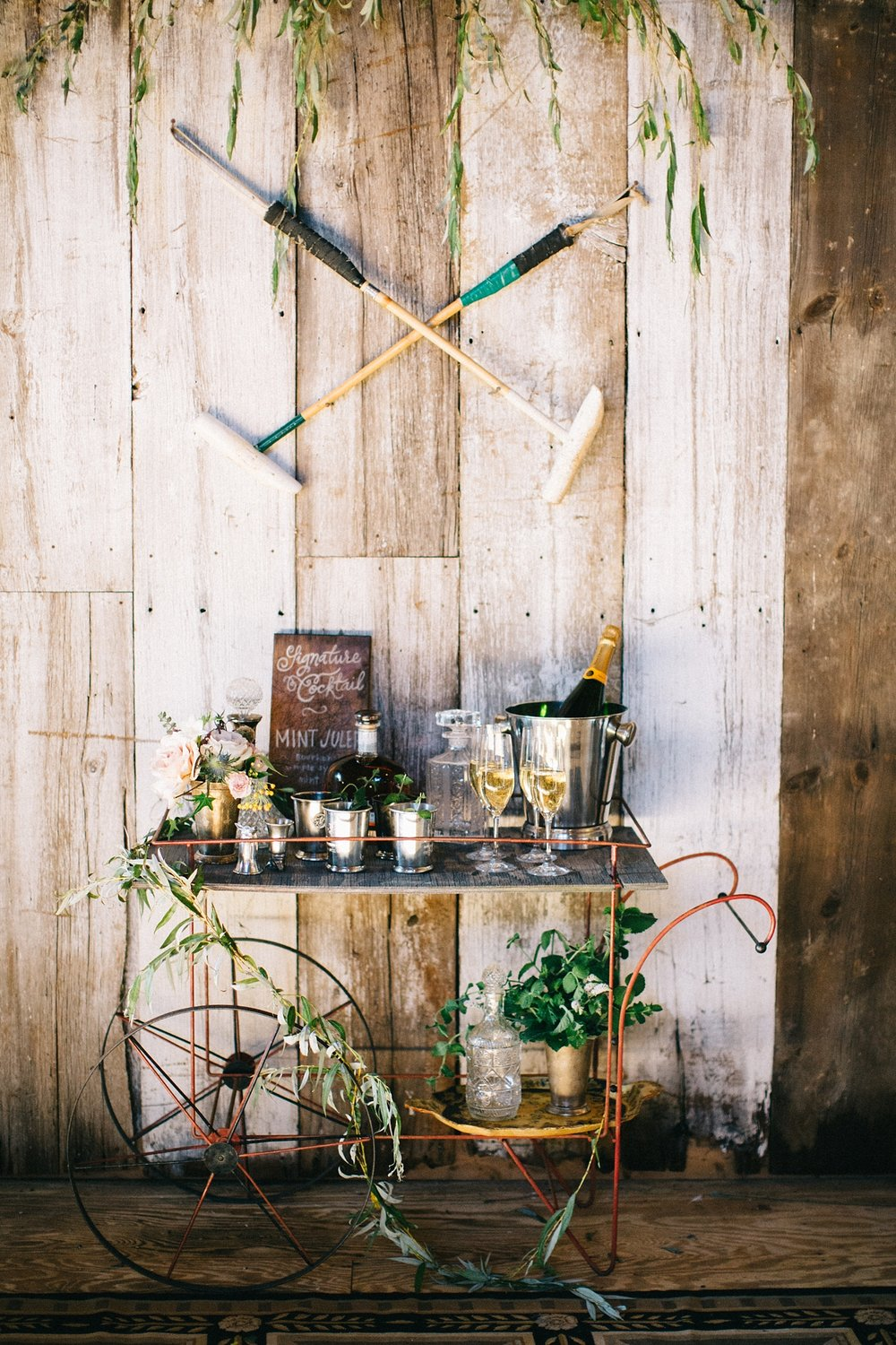 """Every event needs a signature cocktail, and nothing says """"equestrian"""" like a Mint Julep. We decked out this barn cart from Vintage Vogue Event Rentals with a custom sign and floral styling from Sapphire & Lace. This decor combined with julep and stirrup cups from Powers Polo School made for an excellent authentic experience. The cart was crowned with crossed foot mallets."""