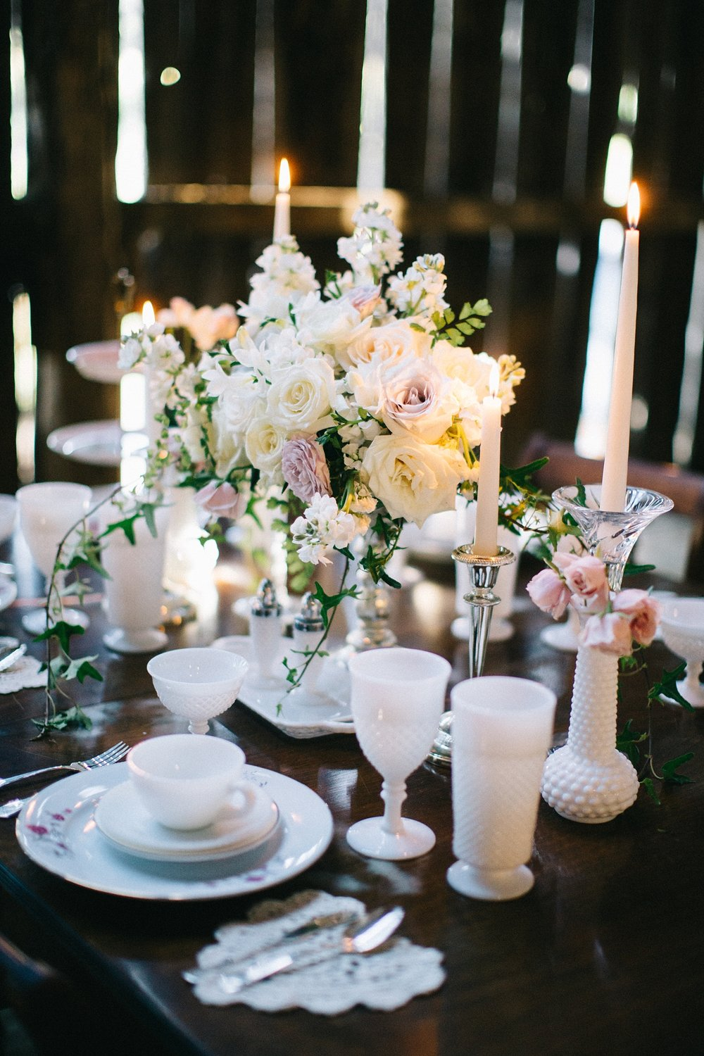 We love the milk glass and delicate floral china pattern that Vintage Vogue styled on one of her rental dinning tables. Those pieces combined with the mercury glass and centerpiece from Sapphire & Lace, and white candle tapers all worked together to really lighten up the space.
