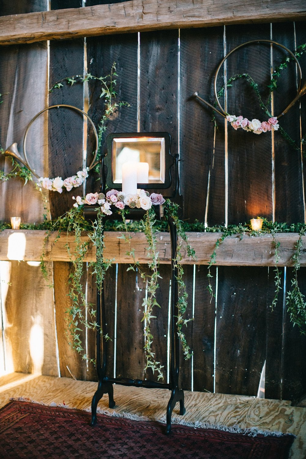 This shoot took place in the beautiful barn at White Horse Livery. With it's hand hewn beams, and light pouring in through the siding, Sapphire &Lace and Vintage Vogue Event Rentals kept the design elements light and airy. Here we have an antique shaving stand acting as an alter with pink, blush, and lavender roses popping out of the drawer, combined with delicate flowing ivy cascading down the legs. The ceremony area felt dreamy. The addition of votive's in mercury glass added a glow that brought out the warmth in the wood.