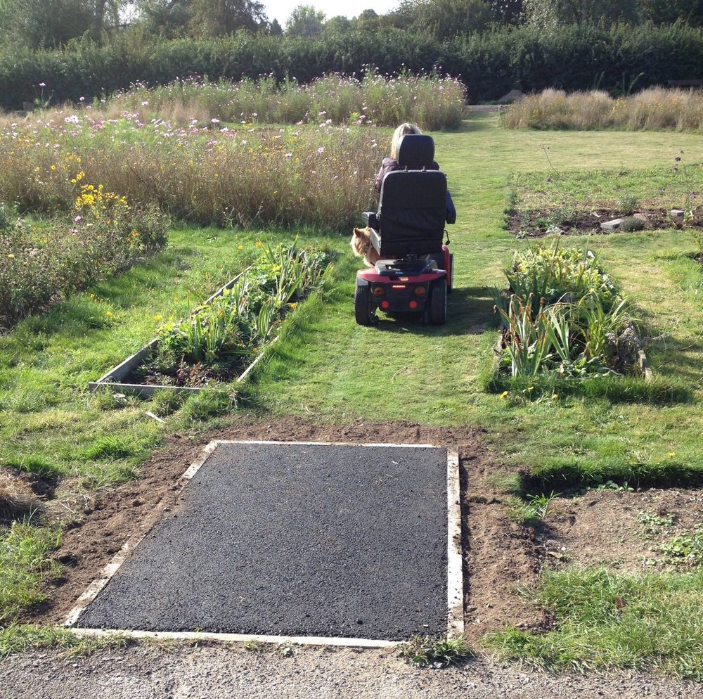 One of our garden volunteers test-driving one of the new ramps. Also very popular with children on small green tractors.