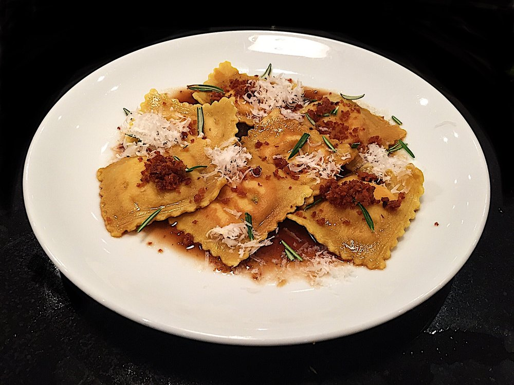 6 Hour Slow cooked Beef Shin Ravioli  Melt in your mouth beef shin, slow cooked in beef stock and red wine. Finished with capers shallots and parsley  Served here with the reduced cooking juice, rosemary olive oil, crispy shallots and parmesan