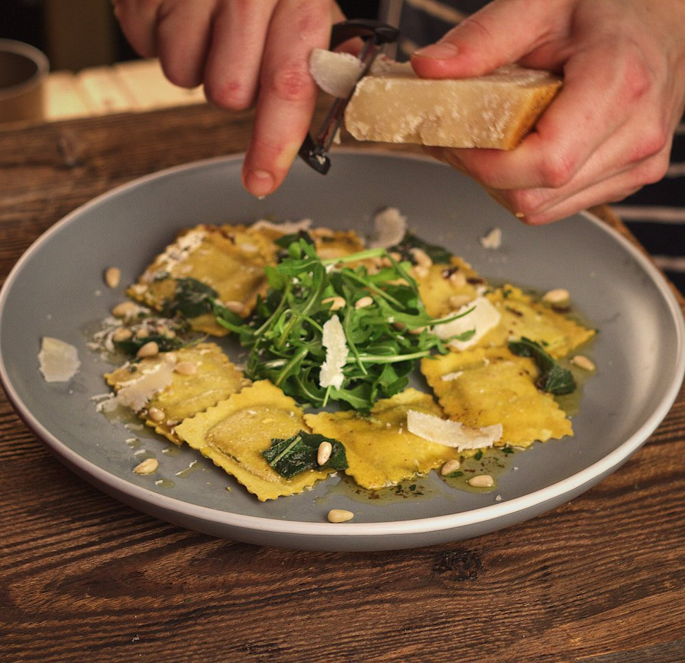 Spinach and Ricotta Ravioli   The Classic done properly. Spinach is wilted with garlic and butter and stirred through ricotta for a creamy delicious filling.  Served here with a dressed rocket salad, minute and pesto.