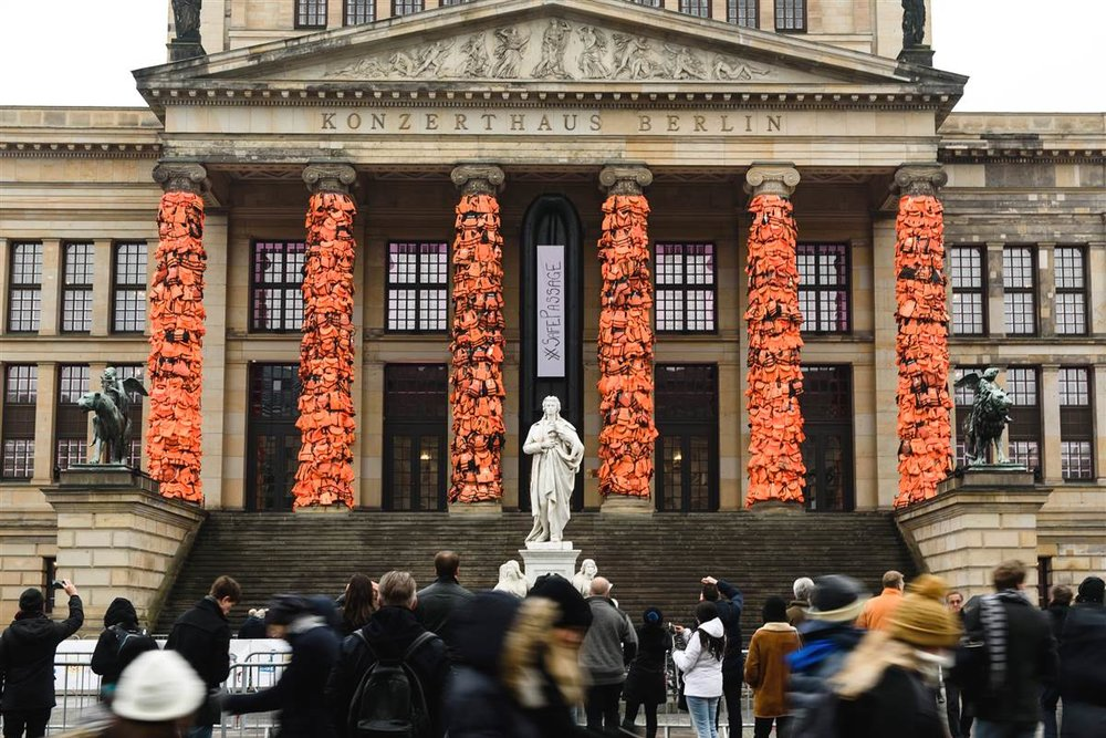 """In this art installation Chinese contemporary artist Ai Weiwei showcases thousands of used life vests by refugees from the Greek island of Lesbos, on February 14, 2016 in Berlin, Germany. The orange vests are wrapped around the pillars of the city's Konzerthaus to highlight the plight of refugees trying to reach Europe."" - The Observer"