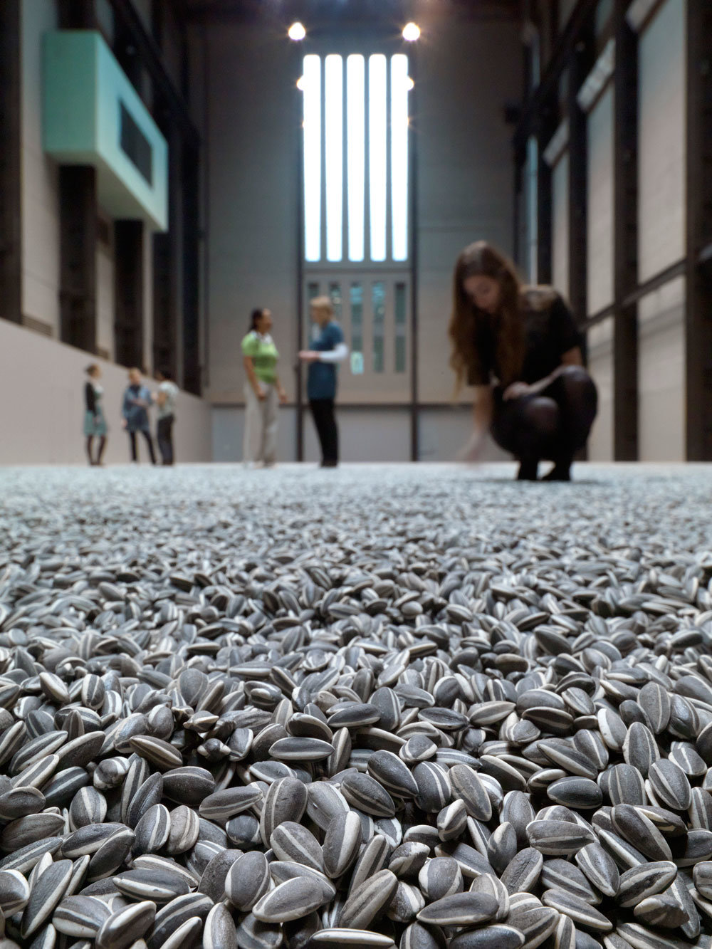"Visitors to Ai Weiwei's art installation ""Sunflower Seeds"" (2010) at the Tate Modern in London, England. The installation was made up of 100 million tiny porcelaine sunflower seeds alluding the globalization and mass production in China catering to western consumerism."