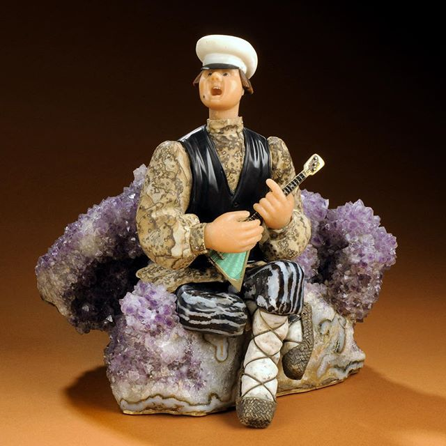 """'Spring' is a #gem #sculpture created by Vasily #Konovalenko, a Soviet #artist and emigre to the United States in the 1980s. 25cm tall, this sculpture depicts a young man serenading his #love on his #balalaika . He is seated on a bed of purple flowers made from #amethyst , hist skin is made from Beloretsk quartz, his teeth and hat from cacholong, his splendid pants from zebra jasper, an #obsidian vest, #jasper jacket, and gold-plated silver lapti shoes. He has sapphire eyes and the pegs of his balalaika are studded with diamonds. Photo 1 by Rick Wicker ©DENVER MUSEUM OF NATURE & SCIENCE 💎 Photo 2 of a group of peasants (circa 1907-1915) was taken by S.M. Prokudin-Gorsky 💎 Photo 3 'Balalaika Player"""" (1930) by Russian #realist and #impressionist , Nikolai Bohgdanov-Belski (1868-1945) 💎 Photo 4 'Russian Boy with Balalaika' (1889) by German artist Wilhelm Amandus Beer 💎 Photo 5: 'Virtuosos' (1891) oil painting by Nikolai Bogdanov-Belsky 💎 Photo 6: 2014 Balalaika-themed stamps 💎 Photo 7 Tsarevich Alexei Nikolaevich #romanov as an infant playing balalaika with cadets on board the Imperial Yacht Standard c. 1907 💎 Photo 8: Photo of renowned #musician and #composer Vasily Vasilievich Andreyev (1861-1918). Andreyev was responsible for the modern development of the standardized balalaika in the 1880s and is considered the father of the academic #folk instrument movement in Eastern Europe. He arranged #russian folk songs for orchestra as well as writing original compositions. He is also known for having revived the gusli, and autoharp. 💎 Photo 9: 1942 photo of a Russian folk music group 💎 Photo 10: 1986 photo by Martin Koenig of Balalaika Russe, American music group, the self described """"preferred band of the Russian nobility emigre society"""". This gives you an idea of the size differences of different balalaikas and the domra (round bodied instrument). #коноваленко"""