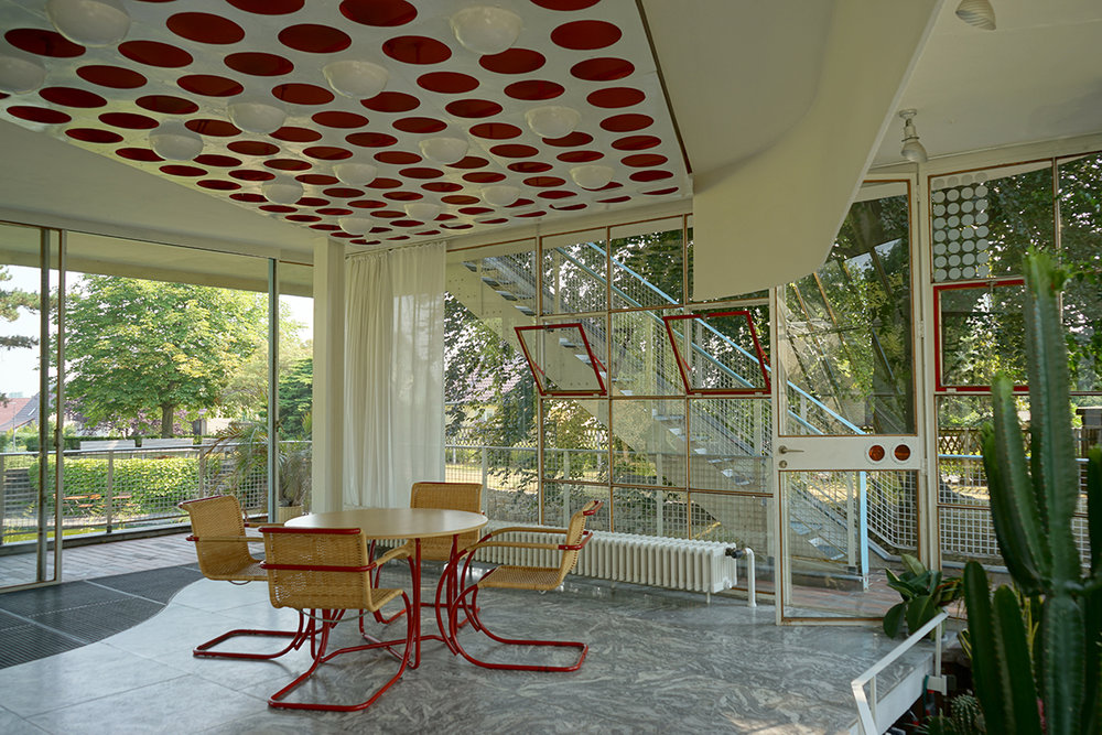 The colored glass portholes on the doorframes of the Schminke House by Hans Scharoun were at a height that the children could look through. Helga recalls running from door to door within the house to look at the world through different colors.