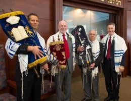 Sister Scrolls from Prestice held by Art Newman of Temple Israel; Jeffrey Ohrenstein, Chairperson of the Memorials Scroll Trust, London; Bob Sofer of Temple Sinai; and Rabbi Joseph Meszler of Temple Sinai.