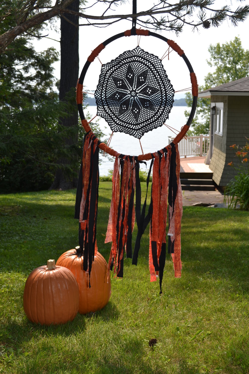 I call this my nightmare catcher. You can make them from an old bicycle tire rim, a vintage dollie painted black, some yarn and scraps of fabric. Hang them in the trees around the house, great for a Halloween party.