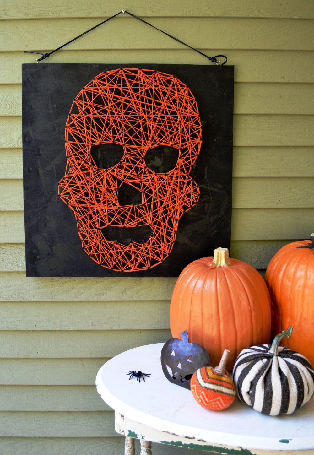 This Halloween Skull wall hanging took me less than 2 hours. I used a scrap of plywood we had lying around-- painted it black and then outlined a skull head in chalk, then using my drill, screwed in screws (only 1/2 way) and then wrapped the screws in orange yarn! Is there glow-in-the-dark yarn? Hmmmm...that would be cool too!