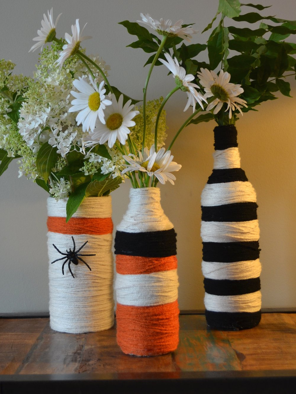 Don't forget the flowers! These Halloween craft recycled bottles and jars are so fun to make. I just used yarns and a hot glue gun. If you are going to a party -- it makes a great gift and some awesome decorations.