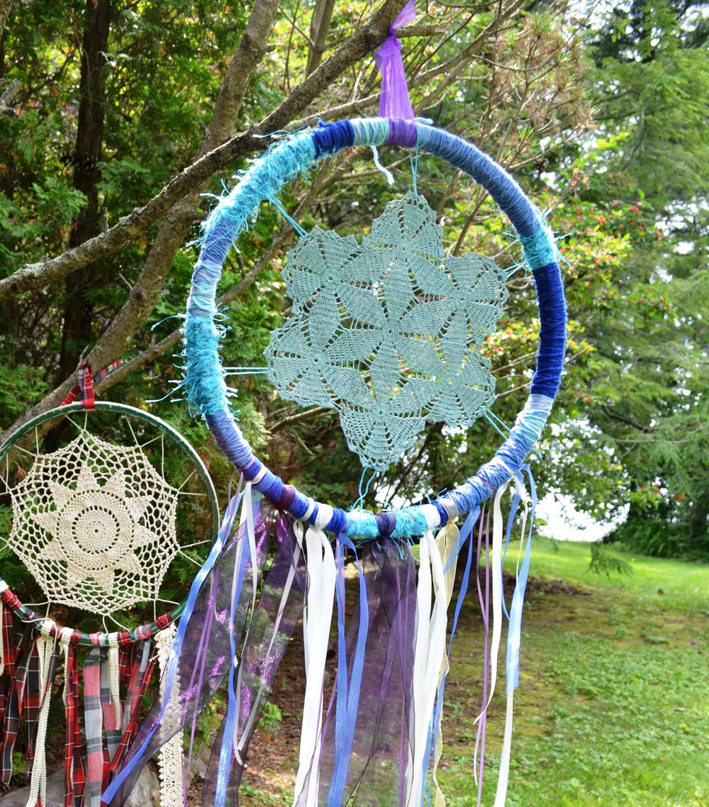 An old tire rim, some ribbons, Grandma's dollies, and some yarn and you can hang these beauties above any bed.