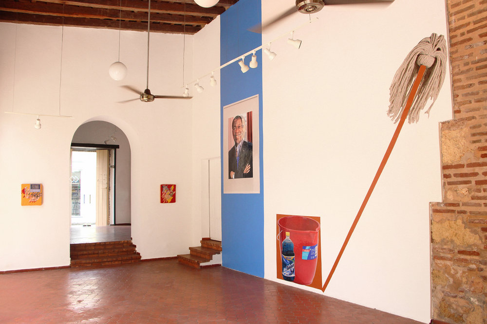"Semi-Gloss house paint; Vinyl decal 2018   Installation view at Casa Quien Gallery in the Dominican Republic. Pictured ""Obama/Gomez"" a photoshopped image of former US President Barack Obama and Dominican leader of the Revolutionary Party of the Dominican Republic Jose Francisco Peña Gomez: known as the man of the people, voted to office by an outstanding majority and lost to a rigged election, a controversial subject still to this day. A red bucket and fabuloso cleaning product and  mop."