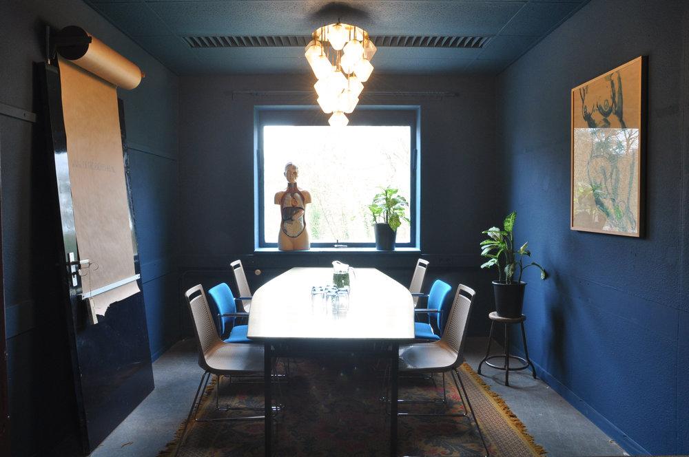 BLAUWE KAMER - Hier kunnen 7 personen prettig confereren.Een dagdeel kost net als alle andere kamers €88,- (4 uur of deel daarvan). Ook kost een hele dag €132,-Onder een enorme jaren 70 plafonnière kan in deze sjieke donkerblauwe kamer serieus vergaderd worden aan een ooit gouden tafel. Aan de muur hangt, even blauw als de muur, rustig een naakt te hangen.Gratis Wifi en gratis parkeren behoren tot de basis, daarnaast bieden we in overleg aanvullende audiovisuele middelen. Er staat een mans grote flipover met kleurrijk schrijfgerei. Een vergader-, lunch-, koffie- of aansluitend borrelarrangement wordt op maat verzorgd.Wil je deze zaal reserveren? Stuur een mail met de specificaties naar DOEJEDING at DEGROENEAFSLAG.nl en we sturen als de wiedeweerga een offerte terug.