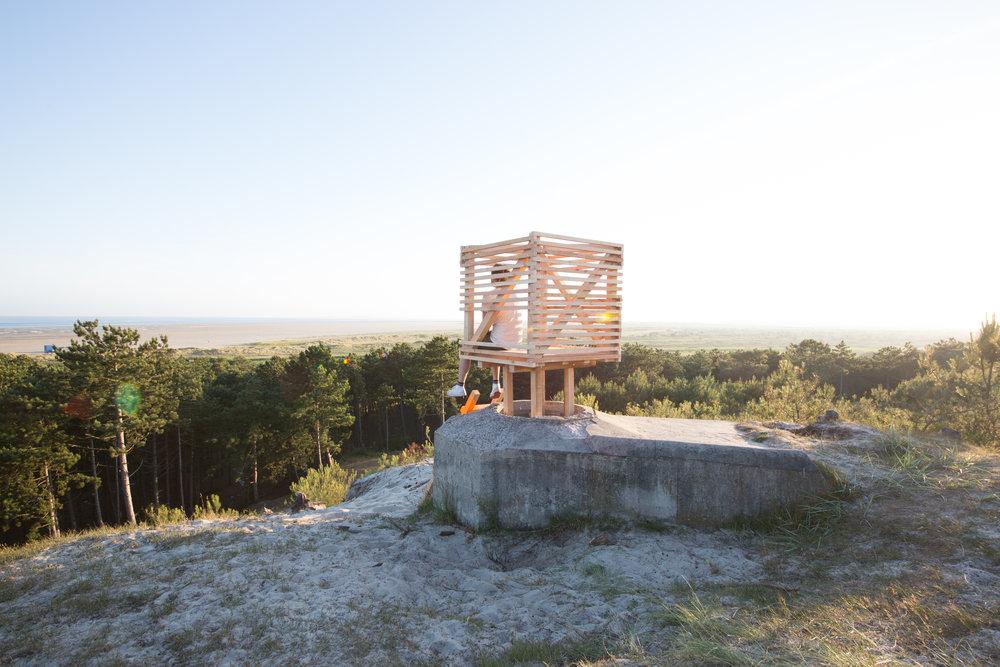 De houten constructie gebruikt de bunker als fundering
