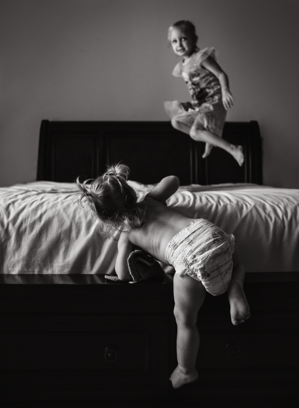 03 monkey see monkey do black and white before and after toddler girl sisters playing on bed jumping natural light window light edmond ok oklahoma city lifestyle photographer (2).png