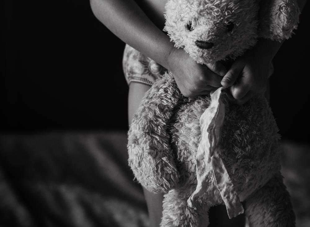 02 bear girl clutching stuffed bear black and white natural light window light lifestyle portrait edmond ok photographer oklahoma city