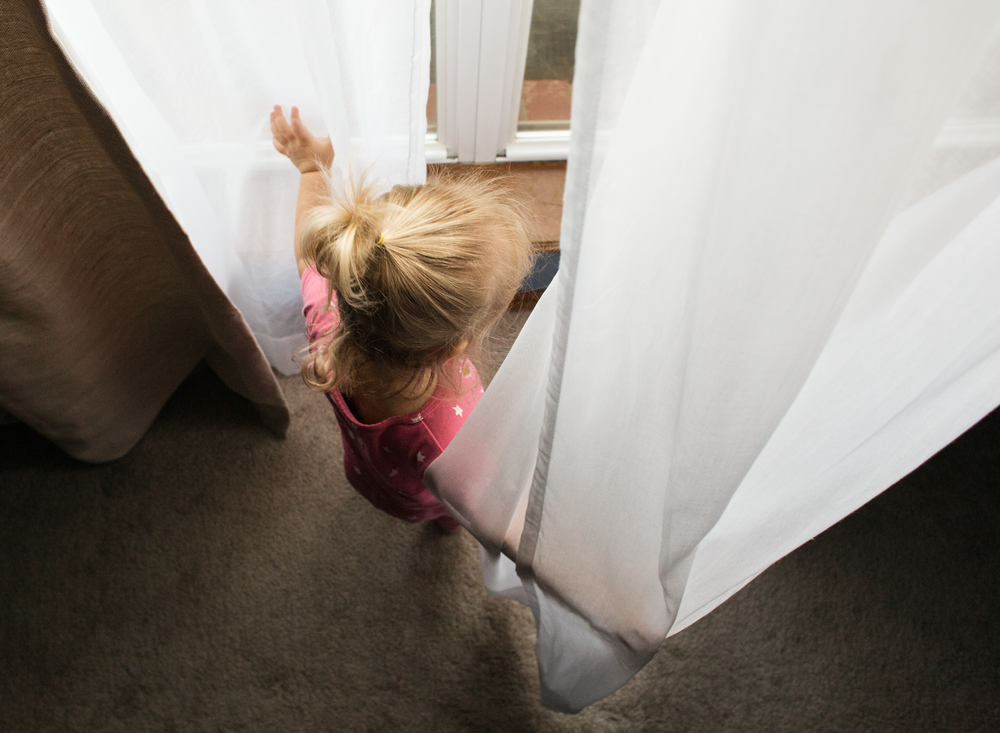 05 hide and seek toddler girl window curtains natural light lifestyle edmond ok photographer oklahoma city kate luber (5).png