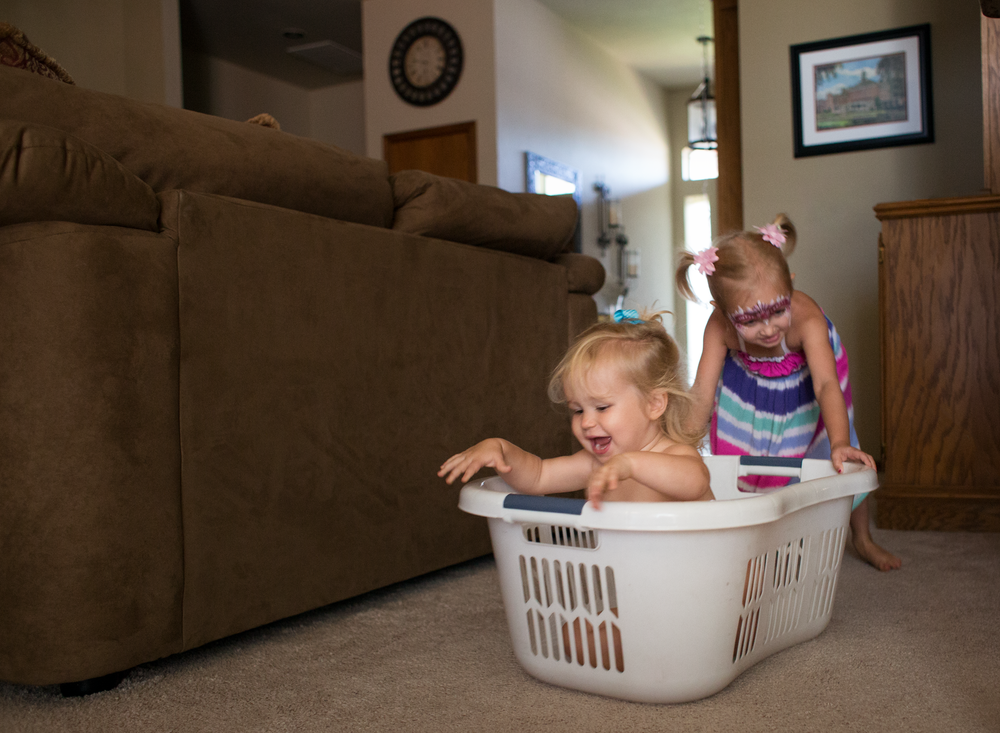 01 laundry races children siblings sisters laundry basket playtime edmond ok photographer oklahoma city lifestyle natural light (5).png