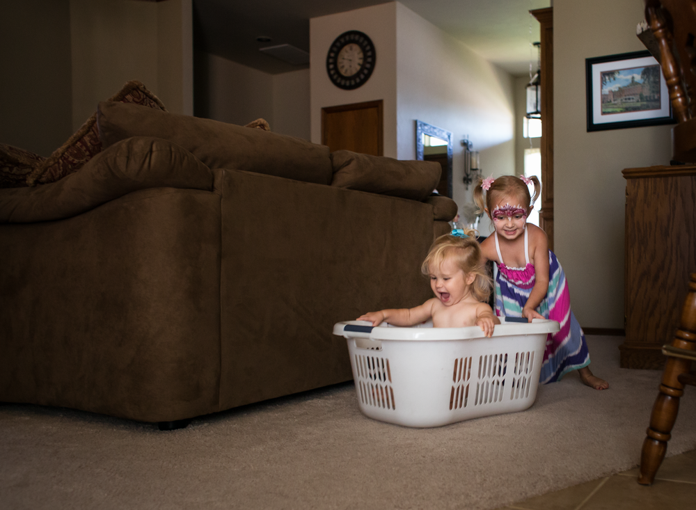 01 laundry races children siblings sisters laundry basket playtime edmond ok photographer oklahoma city lifestyle natural light (11).png
