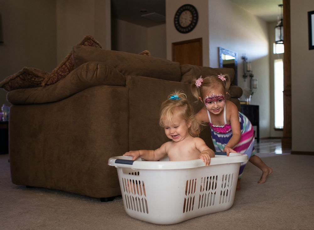 01 laundry races children siblings sisters laundry basket playtime edmond ok photographer oklahoma city lifestyle natural light (13).png