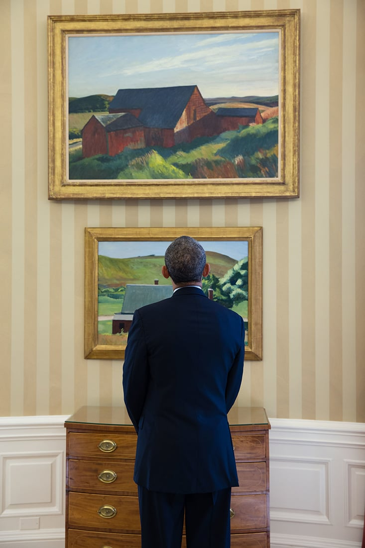 President Barack Obama looks at newly installed Edward Hopper paintings on loan for display in the Oval Office, Feb. 7, 2014. The paintings are Cobb's Barns, South Truro, top, and Burly Cobb's House, South Truro. (Official White House Photo by Chuck Kennedy).