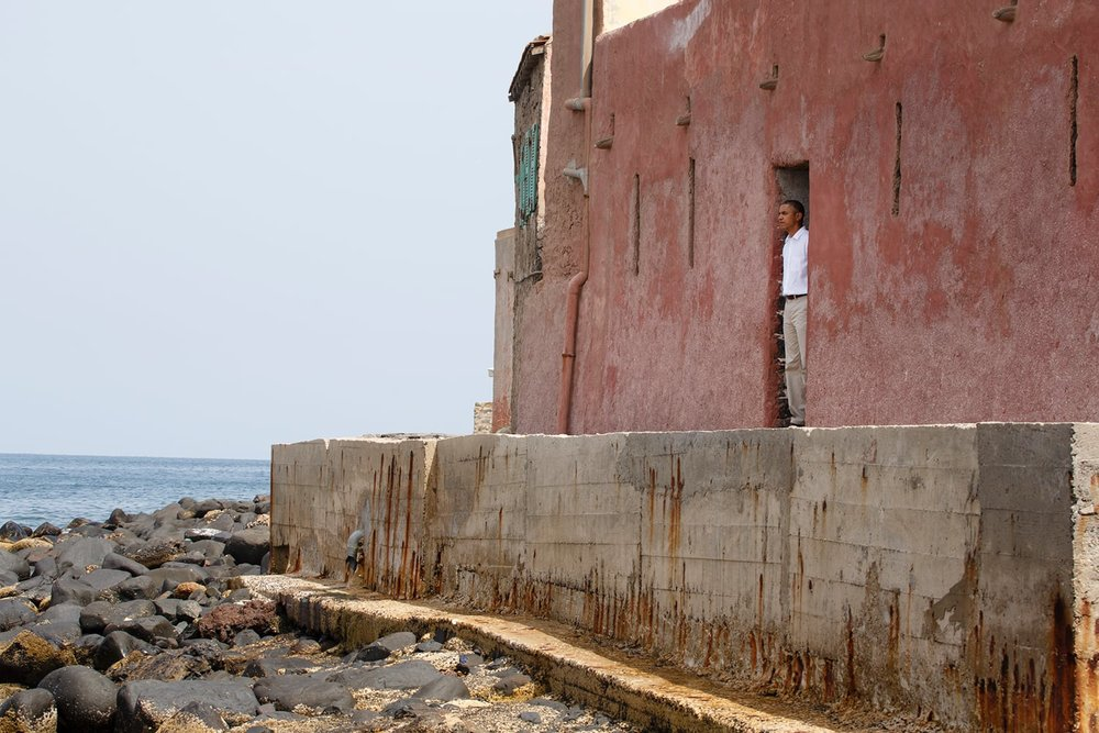 "President Obama, stands in the ""door of no return"" on Senegal's Gorée Island, where captive Africans were led as slaves onto ships bound to America. (Official White House Photo by Chuck Kennedy)."