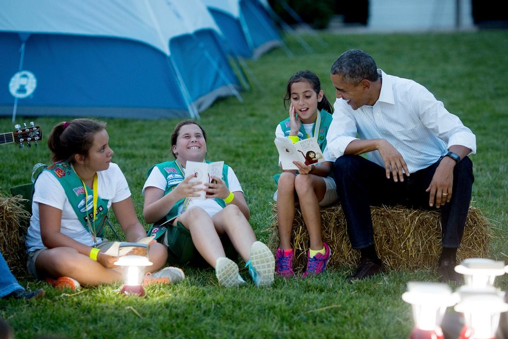"President Barack Obama and First Lady Michelle Obama sing songs with Girl Scouts during the White House Campout, as part of ""Let's Move! Outside"" on the South Lawn. 2015. (Official White House Photo by Chuck Kennedy)."