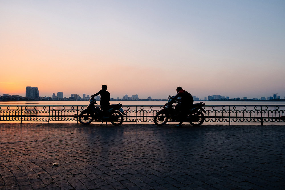 Locals pull over to enjoy the sunset in Hanoi, Vietnam