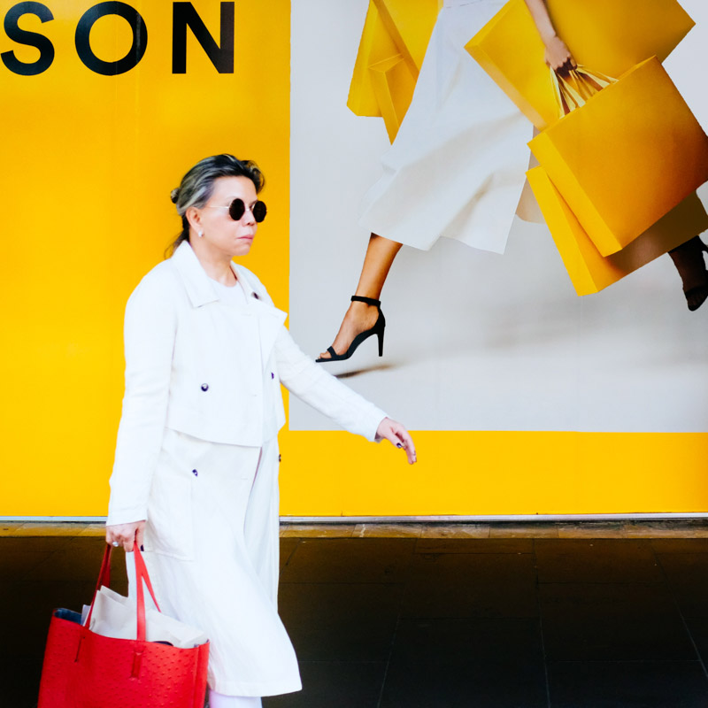 A woman walks past a billboard outside a large department store in the Bourke Street Mall in Melbourne