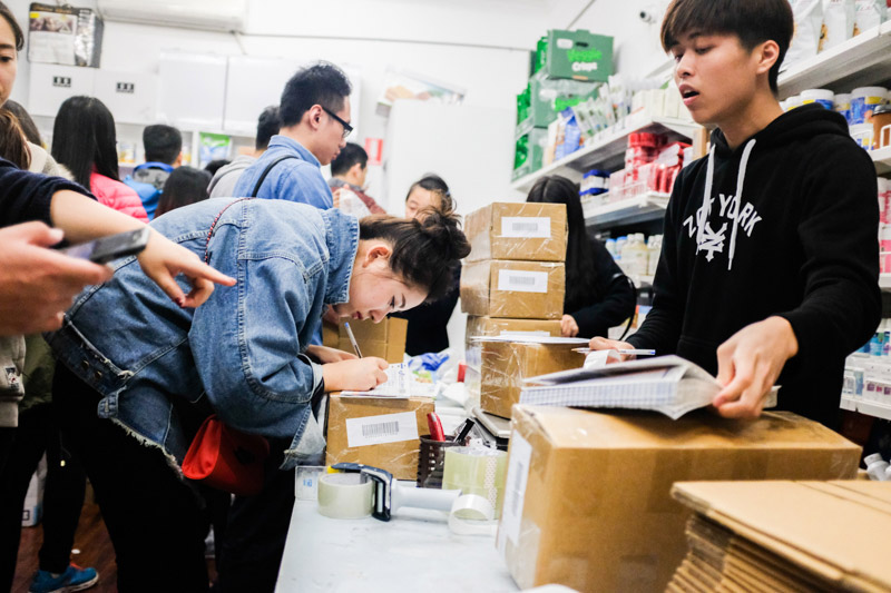 A customer surrounded by packed boxes to be mailed to China fills in a courier docket at the 'Chang Jiang International Express' store in Melbourne. Asanka Brendon Ratnayake for The New York Times.
