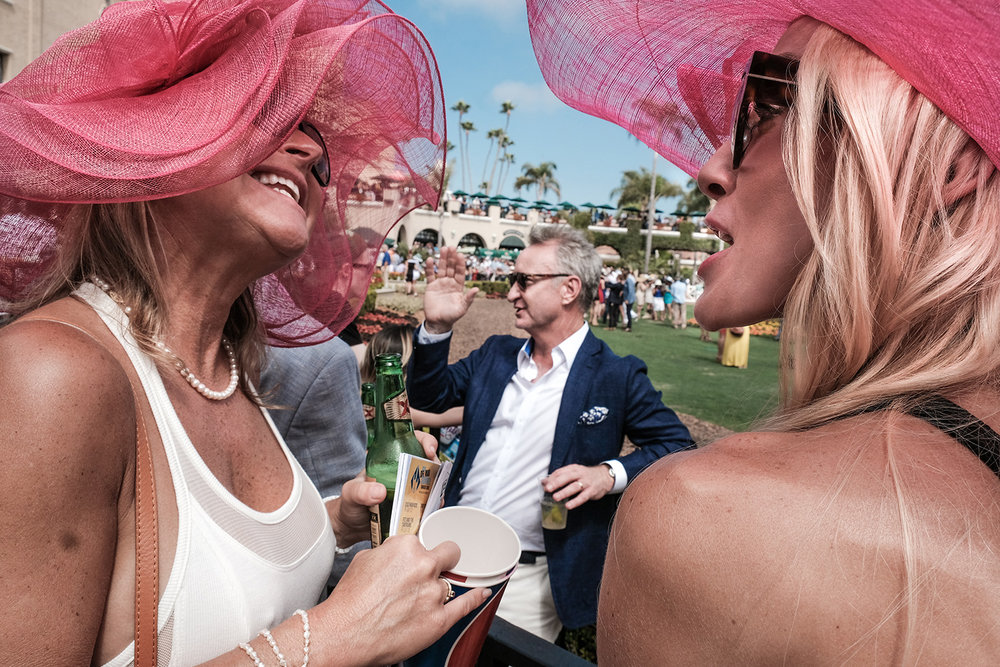 Two women have an animated discussion at the Del Mar Thoroughbred Club in Del Mar, CA on opening day, a big social event.