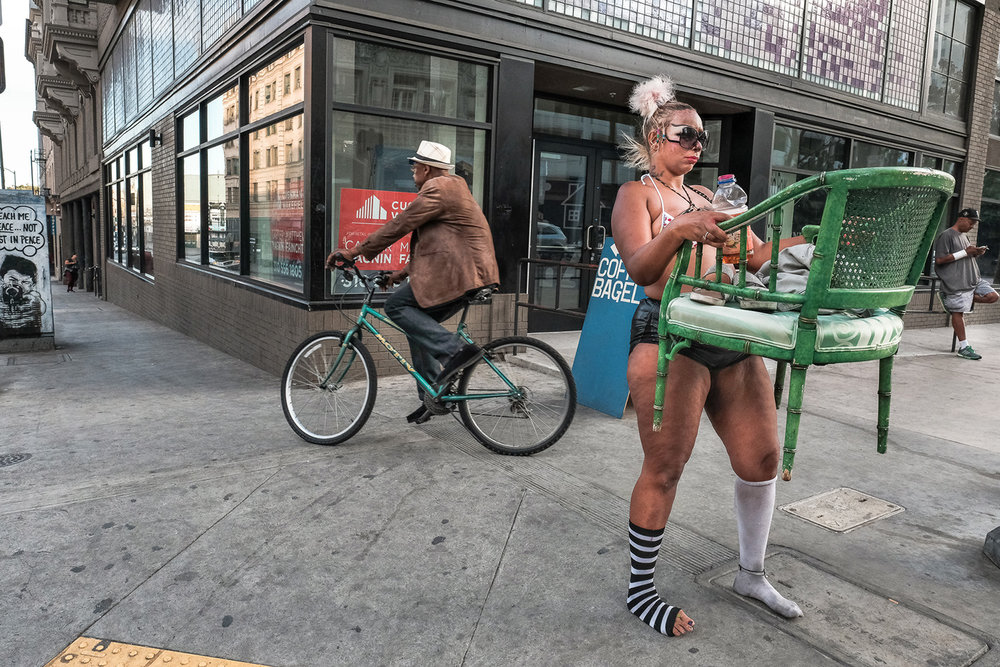 5th And Main St — a woman carries green chair, sits in various locations to solicit donations.