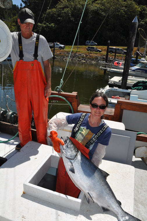 Laura pulling a King Salmon from the fish hold
