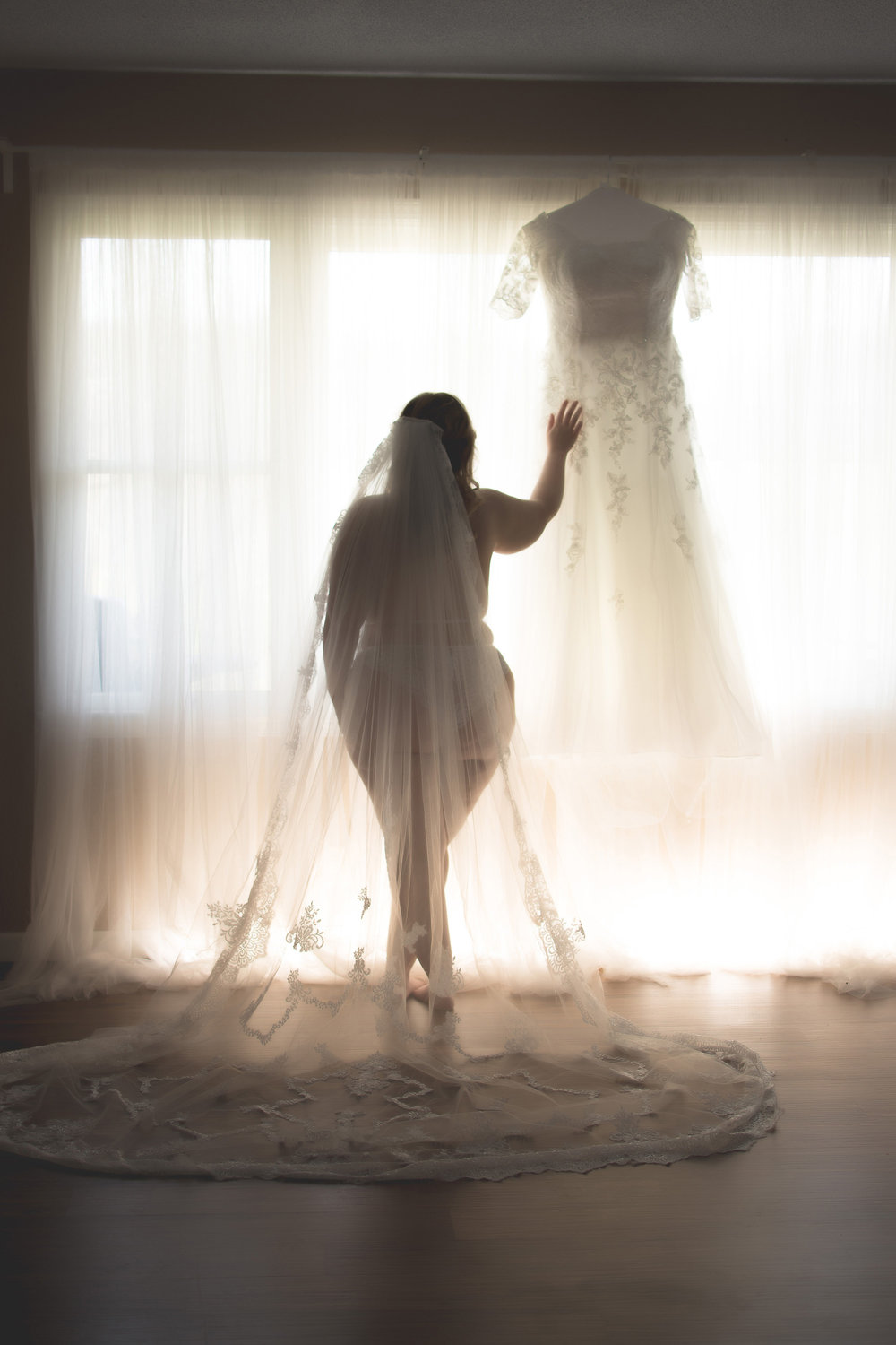 Bride in lingerie and veil looks at wedding dress