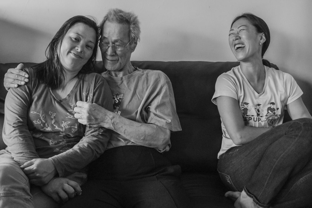 Terminally ill Chinsoo Kim is spending time with family visiting from out of state. He is sitting in his living room with his niece Celeste Pretzel (left) and his oldest daughter Nancy Kim (right). September 2, 2017. Chinsoo Kim's apartment in the Crown Heights section of Brooklyn, NY. Photo by Sung Cho.