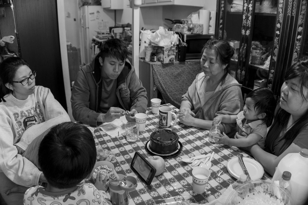The Kim family returns home from a long day that ended with the burial of the family patriarch Chinsoo Kim, who died on 9/14/17 after a yearlong battle with lung cancer. They sit at the dining table with a small cake to lighten the mood and share memories and thoughts. Left to right: Mason Cho (grandson), Janice Kim (2nd daughter), Justin Kim (son), Miwha Kim (wife), Evelyn Cho (granddaughter), Sally Kim (3rd daughter). September 19, 2017. Miwha Kim's apartment in the Crown Heights section of Brooklyn, NY. Photo by Sung Cho.