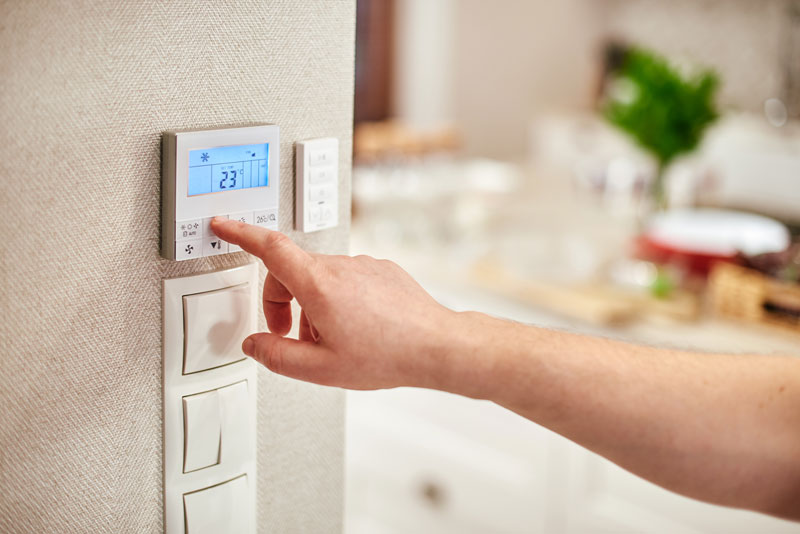 man's hand reaching out to a thermostat