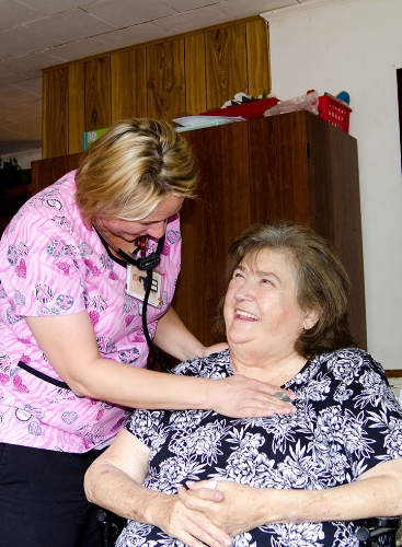Catawba Regional Hospice nurse Madessa Willey examines Cynthia King