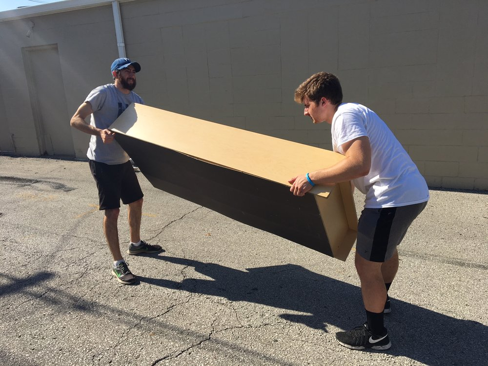 Isaac and Jake hoisting some shelving in the Heat!