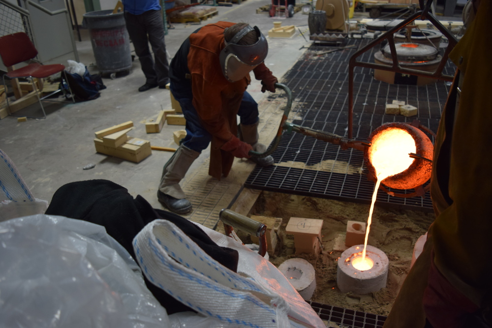 At the foundry, pouring the bronze into the plates' investment mold.