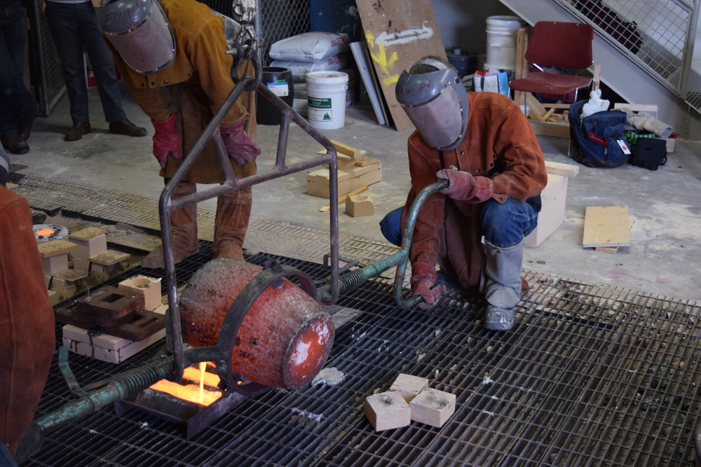 The remaining bronze is poured into ingots. About this time I was unbelievably hot. The heat radiating off the crucible and molten bronze is incredible to feel.