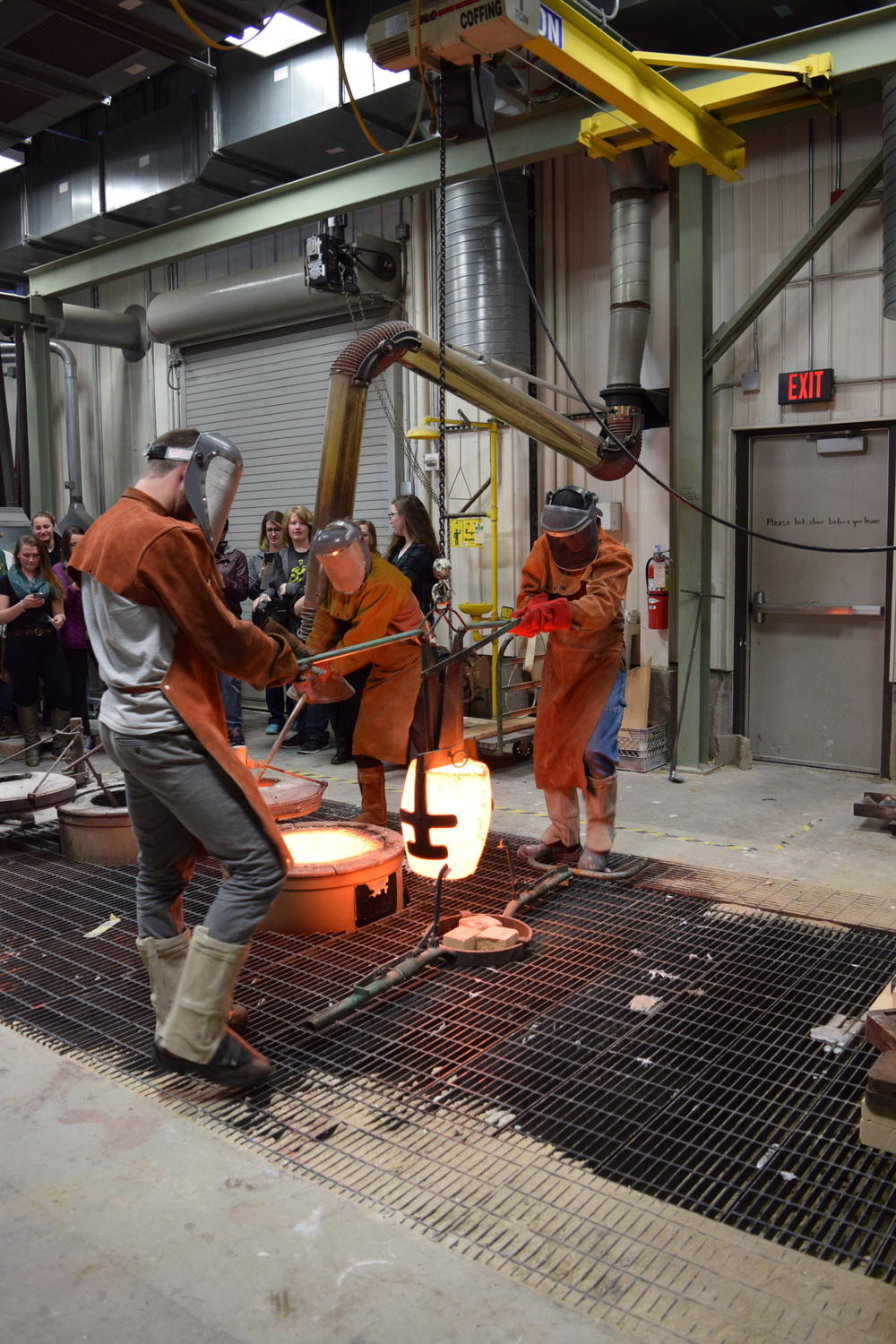 Bringing the bronze crucible out of the forge. A group from a local high school was observing.