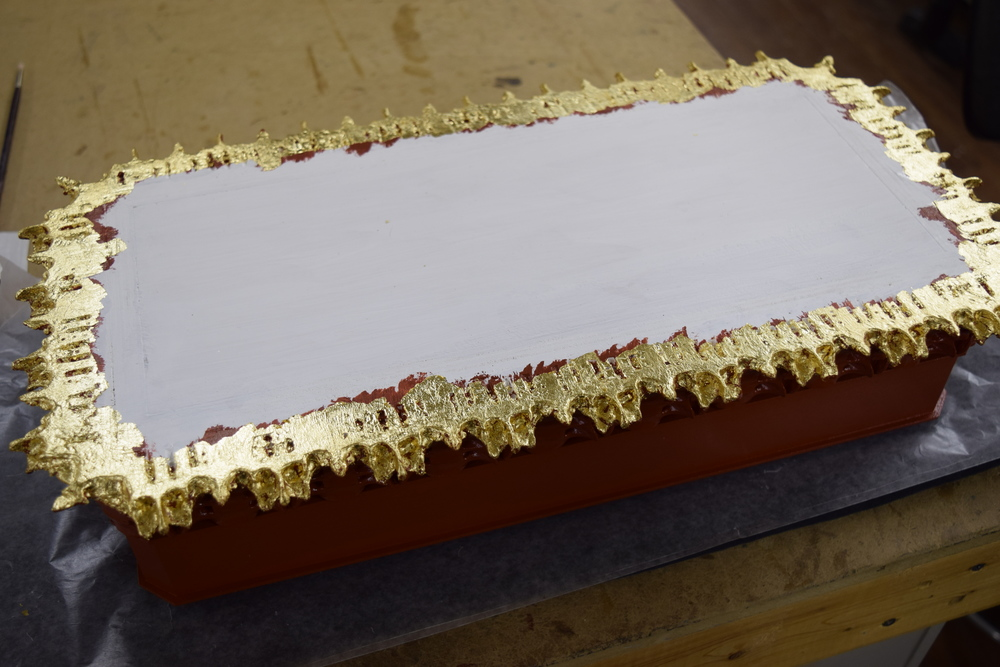 The finished gold leaf on the underside of the base.